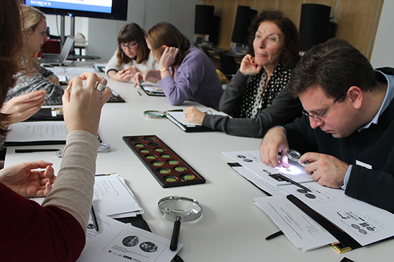 Teachers handling Greek coins from the Ashmolean collection